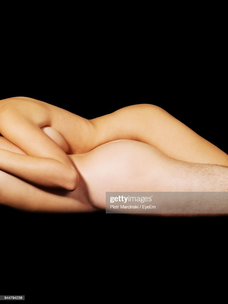 Midsection Of Naked Couple Romancing Against Black Background : Stock Photo