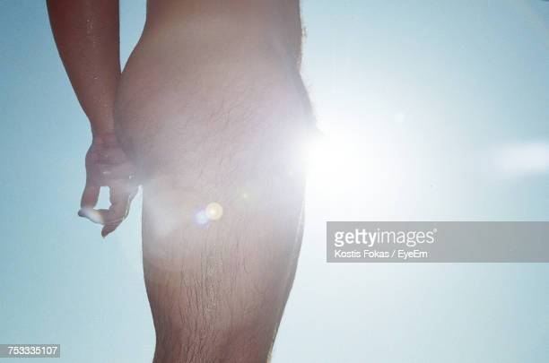 Midsection Of Naked Man Standing Against Sky On Sunny Day