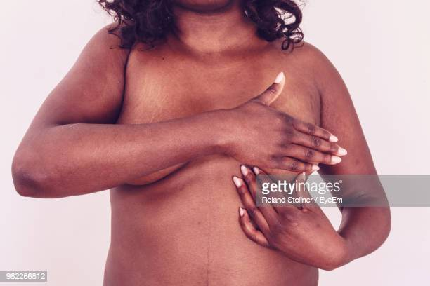 midsection of naked woman against white background - large breasts stock pictures, royalty-free photos & images