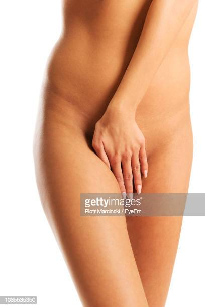 midsection of naked woman covering vagina while standing over white background - intimbereich frau stock-fotos und bilder