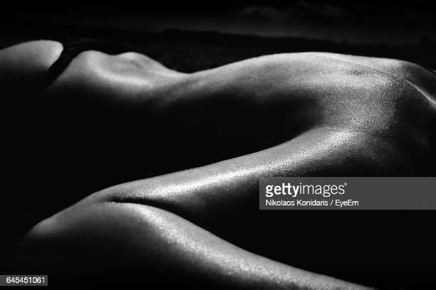Midsection Of Naked Woman Lying At Home
