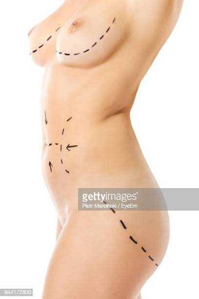 Midsection Of Naked Woman With Markings Against White Background