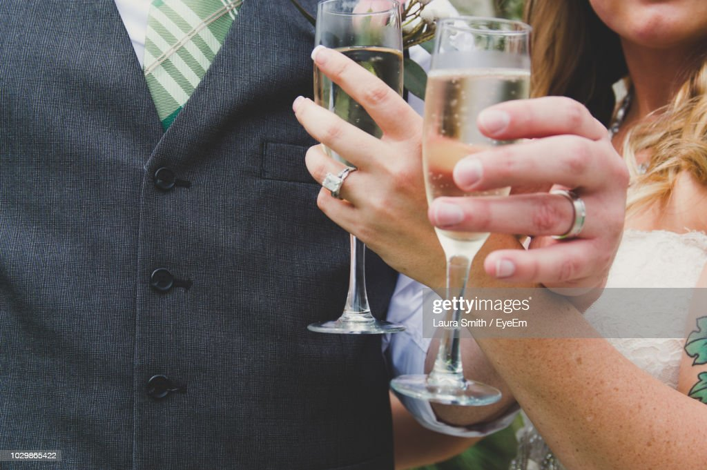 Midsection Of Newlywed Couple Holding Champagne Flutes At Wedding Ceremony : Stock Photo