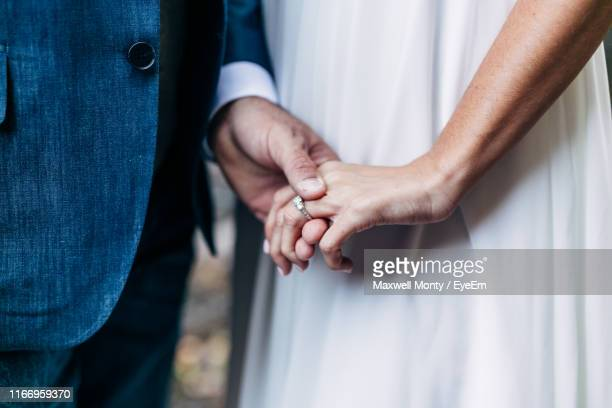 midsection of newlywed couple holding hands - trouwen stockfoto's en -beelden