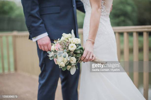 midsection of newlywed couple standing outdoors - wedding stock pictures, royalty-free photos & images