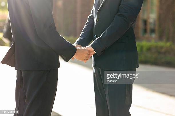 Midsection of newlywed gay couple holding hands