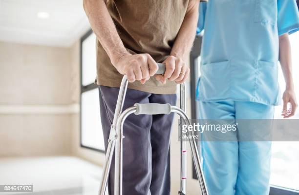 Abdomen de l'infirmière et senior homme avec walker