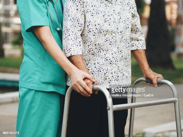 Midsection Of Nurse Helping Patient With Walker