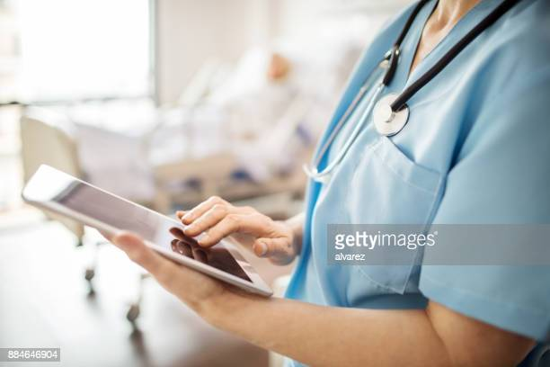 midsection of nurse using tablet pc in hospital - infermiera foto e immagini stock