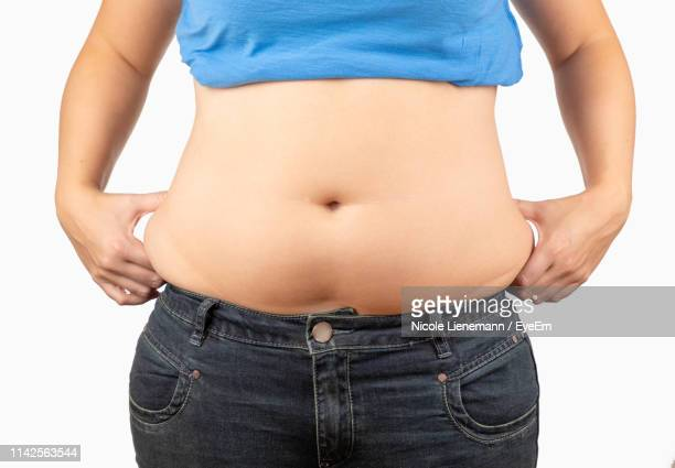 midsection of overweight woman standing against white background - belly button stock pictures, royalty-free photos & images
