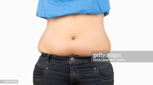 midsection of overweight woman standing against white background - human abdomen stock pictures, royalty-free photos & images