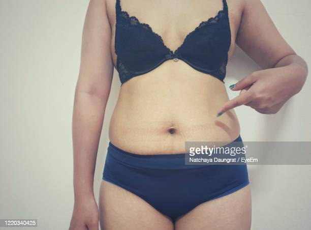 midsection of overweight woman wearing lingerie standing against white background - black slip photos et images de collection