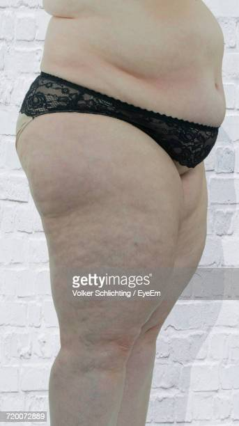 midsection of overweight woman wearing panties standing against white wall - chubby legs stock photos and pictures