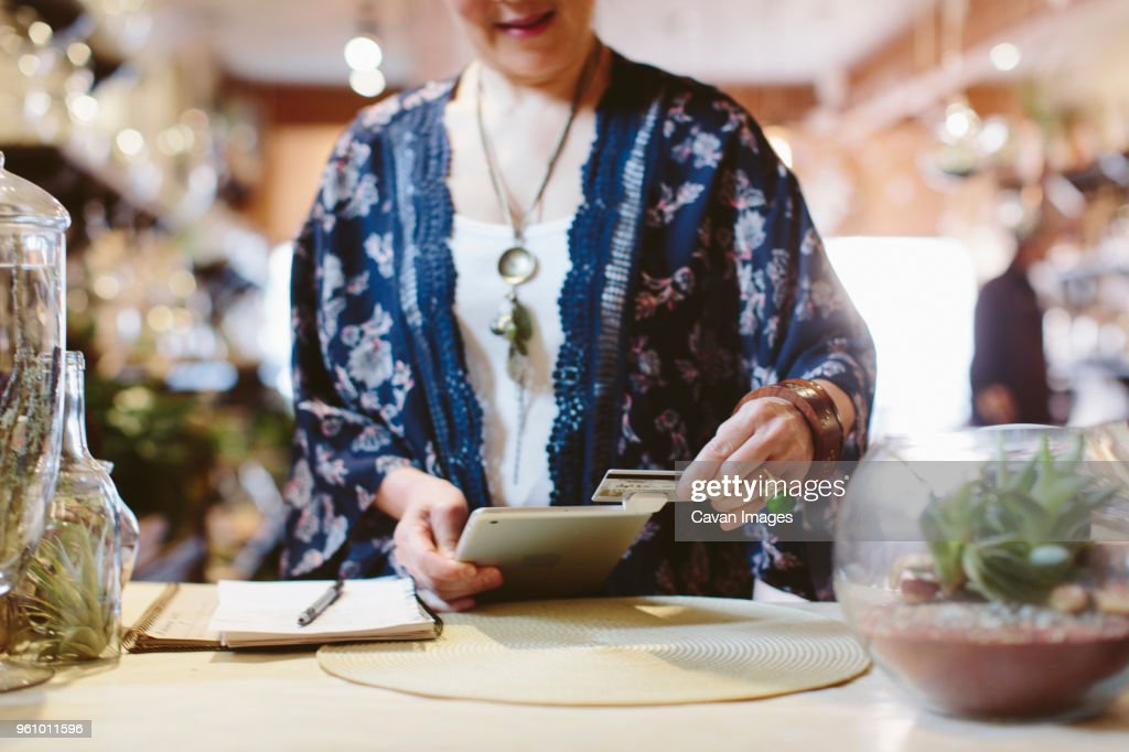 Midsection of owner reading credit card through tablet computer for payment in plant shop : Stock Photo