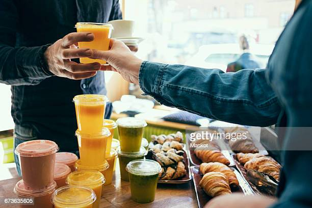 Midsection of owner serving juice to male customer in coffee shop