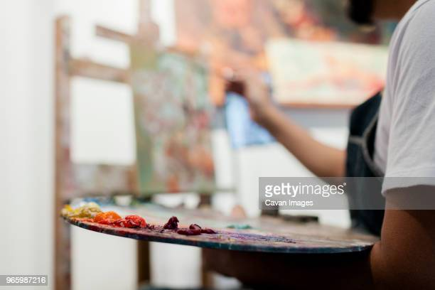 Midsection of painter holding palette while painting in studio