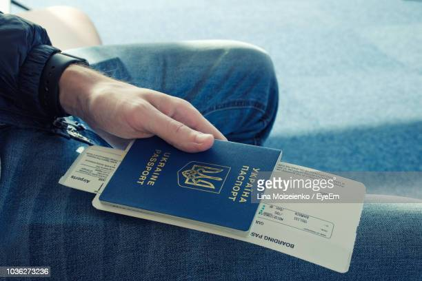midsection of passenger holding passport and ticket - passport stamp stock photos and pictures