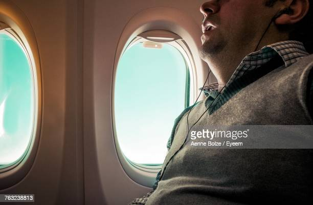 midsection of passenger listening music on headphones while sitting in airplane - mouth open stock pictures, royalty-free photos & images