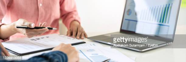 midsection of people discussing on table - finance and economy stock pictures, royalty-free photos & images