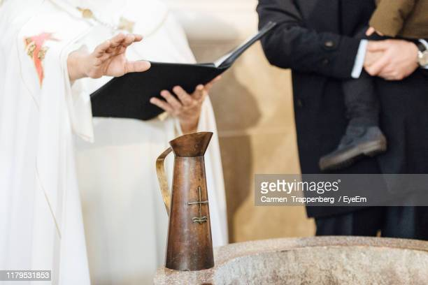 midsection of people doing baptism - catholic baptism stock pictures, royalty-free photos & images