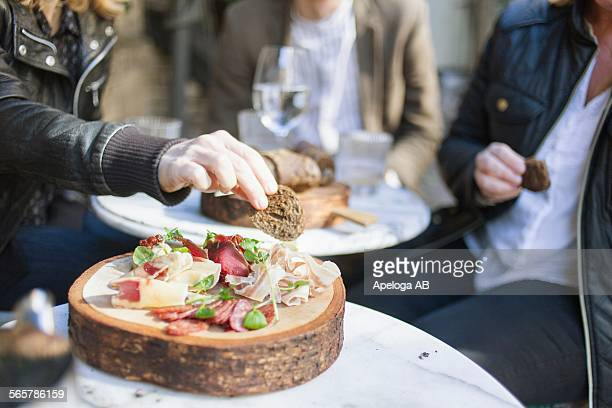 Midsection of people having breads at outdoor restaurant
