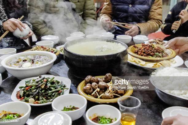 Midsection Of People Having Food At Dining Table