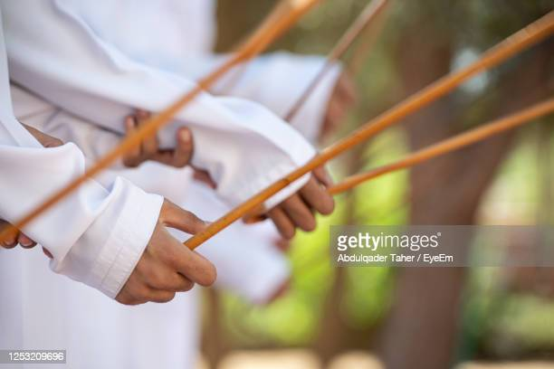 midsection of people holding wooden sticks - tradition stock pictures, royalty-free photos & images