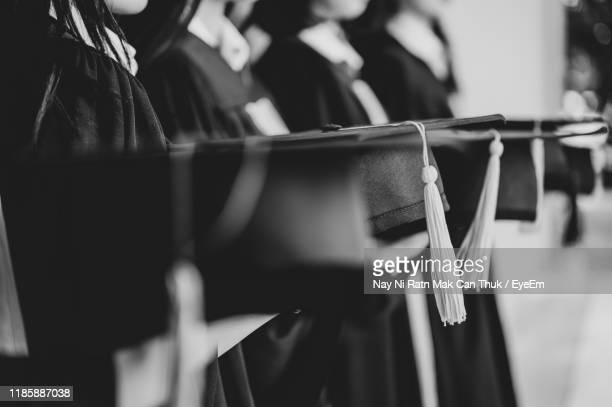 midsection of people in graduation gowns - diploma foto e immagini stock