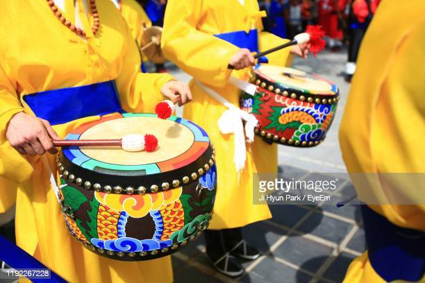 midsection of people playing drums while standing on street during event - celebratory event photos et images de collection