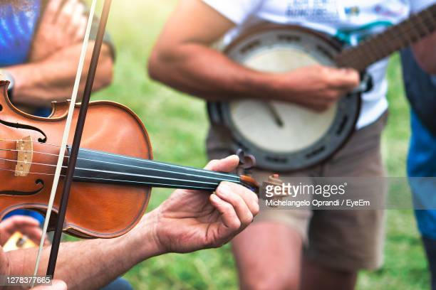 midsection of people playing musical instruments - folk music stock pictures, royalty-free photos & images