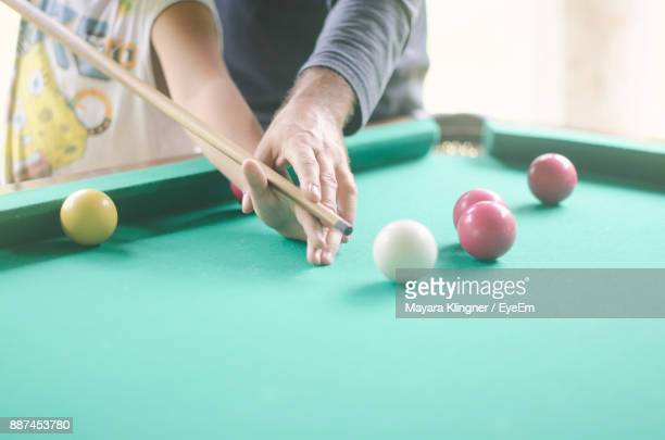 Midsection Of People Playing Pool