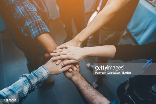 midsection of people stacking hands - unity stock pictures, royalty-free photos & images