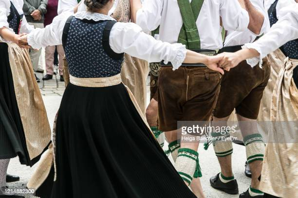 midsection of people wearing traditional clothing dancing outdoors - tradition stock-fotos und bilder