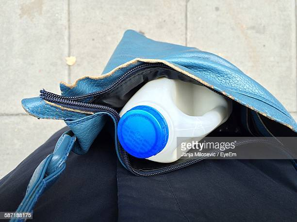 Midsection Of Person Carrying Plastic Milk Bottle In Bag