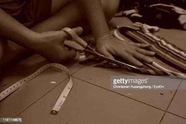 Midsection Of Person Cutting Fabric On Floor