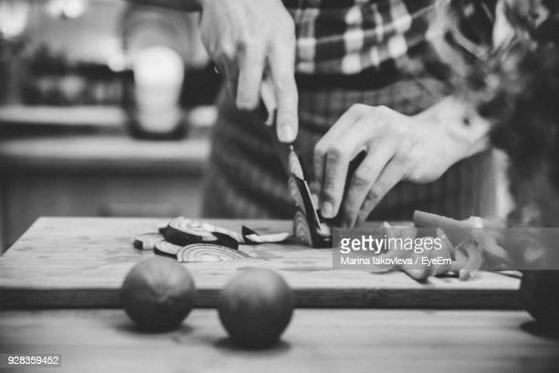 midsection of person cutting vegetable - black and white vegetables stock photos and pictures