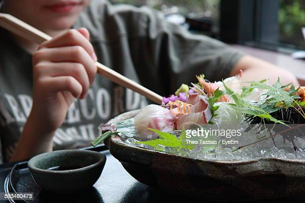 Midsection Of Person Eating Sushi On Table At Home