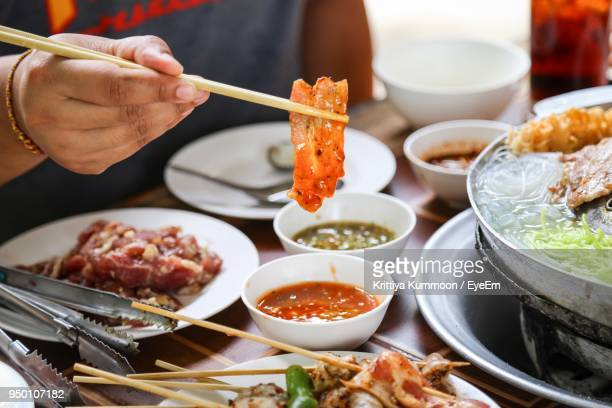 midsection of person having food at restaurant - korean food stock pictures, royalty-free photos & images