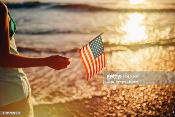 midsection of person holding american flag against sea during sunset - dia do trabalhador - fotografias e filmes do acervo