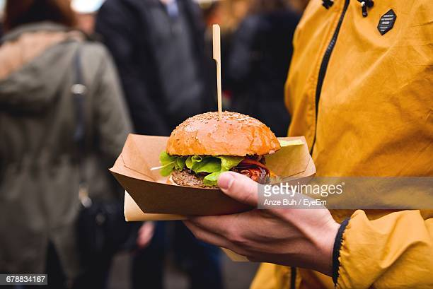 midsection of person holding burger in paper plate - paper plate stock photos and pictures
