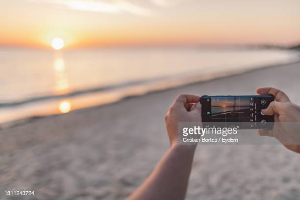 midsection of person holding camera at beach against sky during sunset - bortes stock pictures, royalty-free photos & images