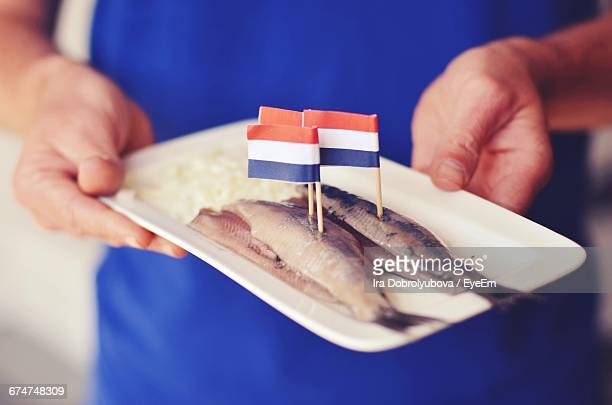 Midsection Of Person Holding Dead Fishes With Dutch Flags
