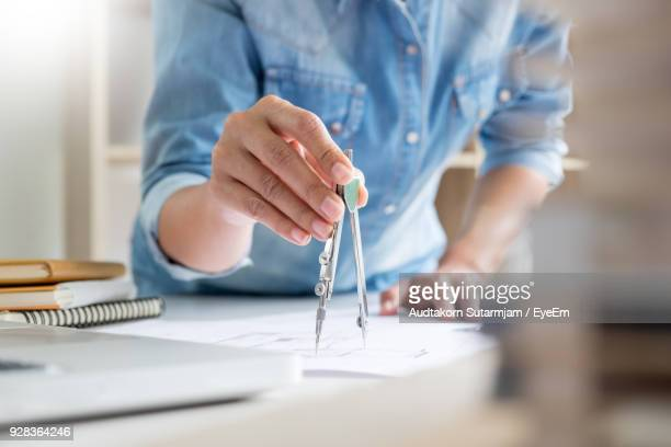 Midsection Of Person Holding Drawing Compass On Paper