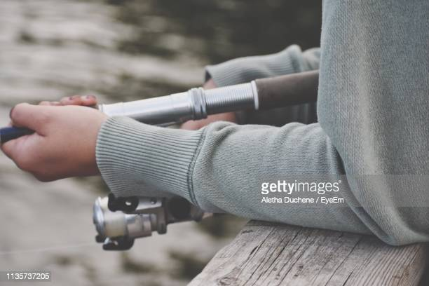 midsection of person holding fishing rod - duchene stock photos and pictures