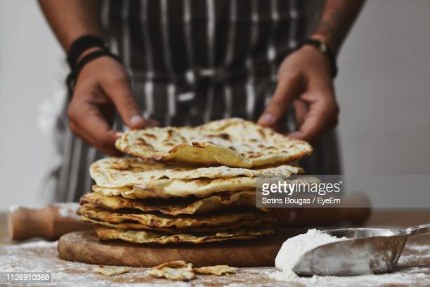 midsection of person holding flat bread - greek food stock pictures, royalty-free photos & images