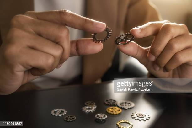 midsection of person holding gear on table - cog stock pictures, royalty-free photos & images