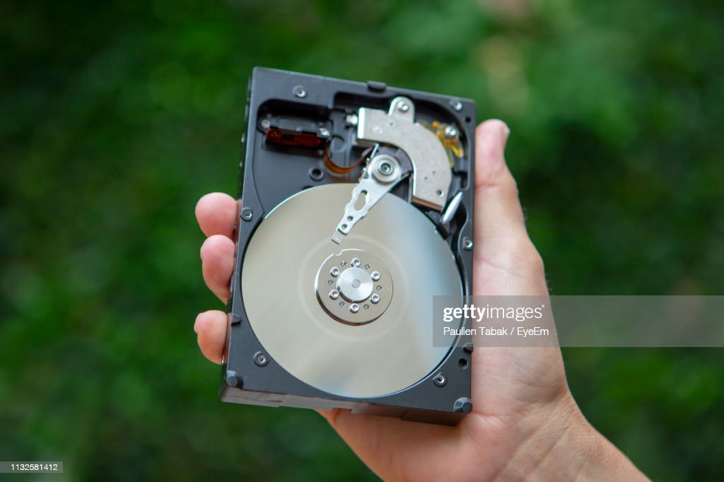 Midsection Of Person Holding Hard Disc Drive : Stockfoto