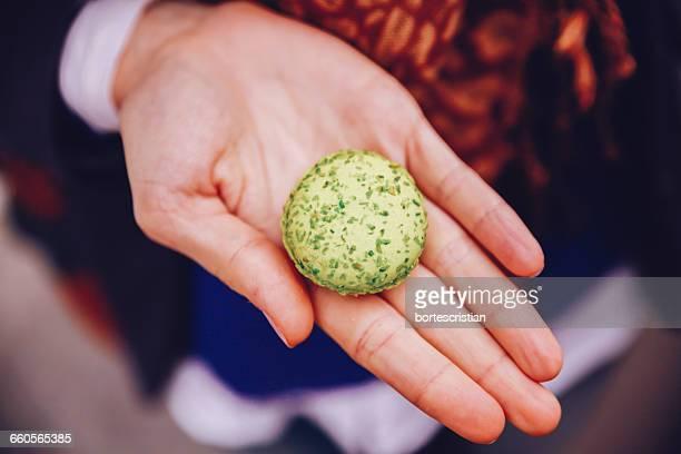 midsection of person holding macaroon - bortes stockfoto's en -beelden