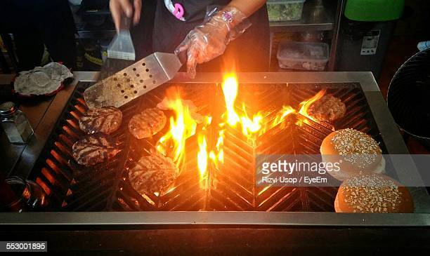 Midsection Of Person Making Burgers On Barbecue Grill