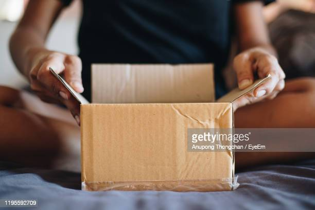 midsection of person opening box - people stock pictures, royalty-free photos & images